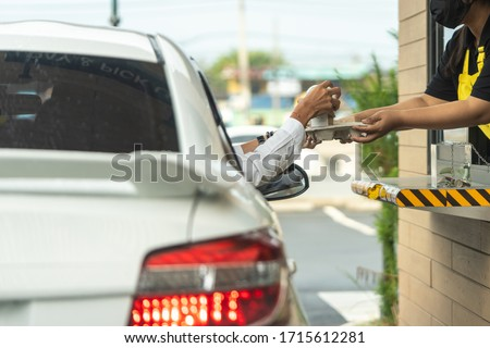 Hand of man from the car is picking a cup of coffee from the salesman by driving through. (Social distancing) Foto stock ©