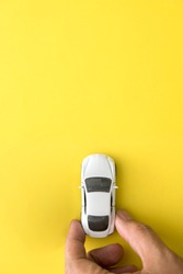 hand of man hold miniature toy cars on the yellow background top view.automobile and transportation concept
