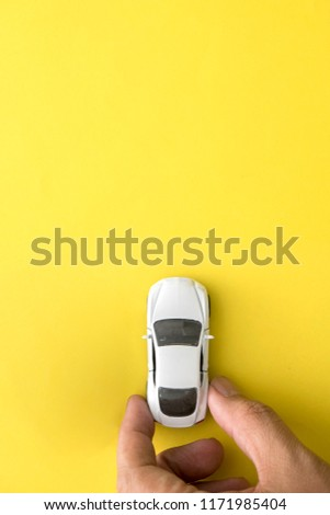 hand of man hold miniature toy cars on the yellow background top view.automobile and transportation concept stock photo