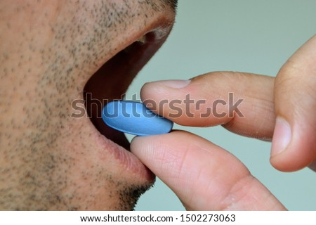 Hand of man holding blue pill. Closeup of a man taking blue medicine pill. Mouth view, illness. Medicine concept of viagra, medication for stomach, erection, sleeping, digestive or drugs
