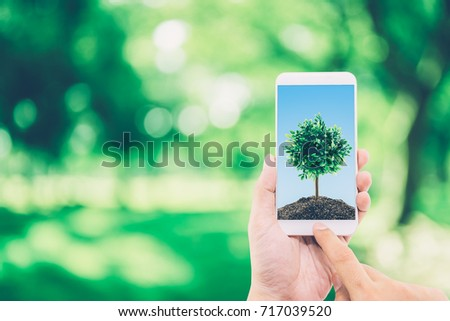 Hand of man holding mobile phone with soil and tree on screen, environment concept. #717039520