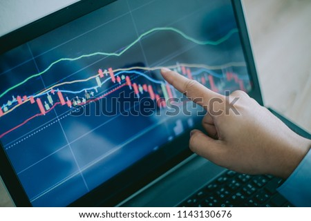 Hand of man point  to the laptop show financial market chart graphic going down.  Stock market concept. #1143130676