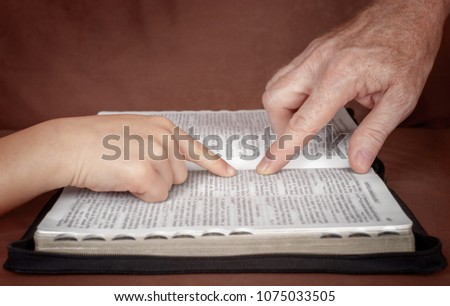 Hand of man pointing something to a child in the Bible book. Teaching a disciple from the Bible.