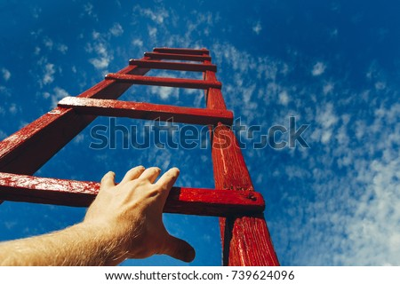 Hand Of Man Reaching For Red Ladder Leading To A Blue Sky. Development motivation Career Growth Concept - Shutterstock ID 739624096