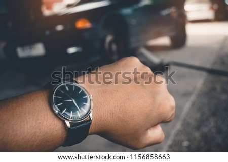 Hand of man\'s Wrist Watch Waiting for the car repair ,Llong time concept.
