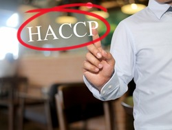 Hand of man touching text HACCP with white color on blur interior background,concept of adoption to promote your business for organization.