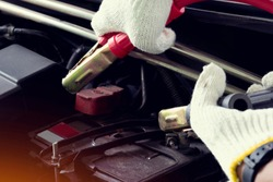 Hand of man wear white gloves second hand, holding the car battery terminal jumper cable.