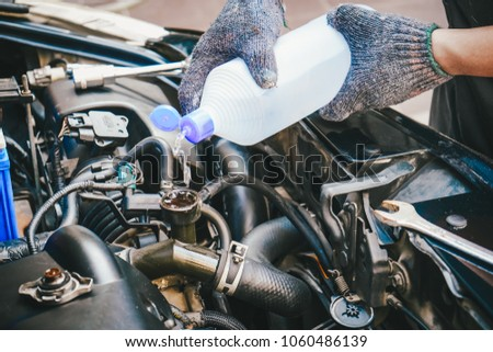 hand of Mechanic Check water in Car radiator and Add water to car radiator, selective focus