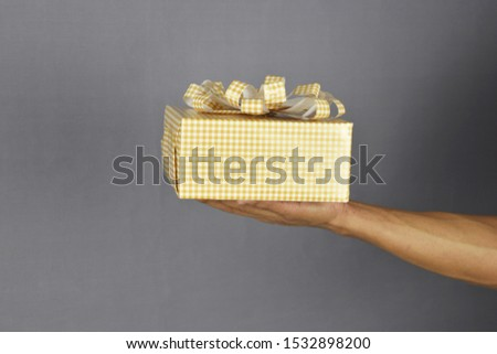 Hand of men holding present gift box package on grey background. Life events celebration congratulation love care concept.