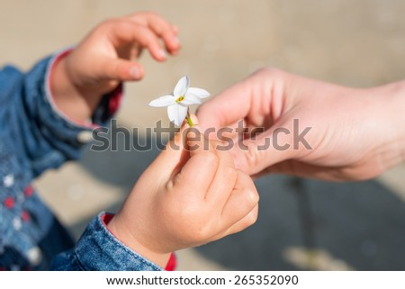Hand of mother handing flowers to child