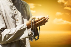 Hand of muslim people praying with sunset background
