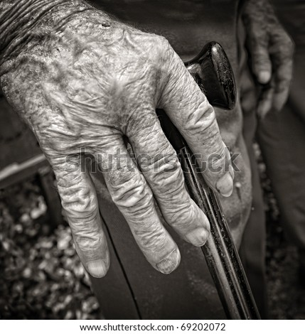 Hand of old man with arthritis supported with walking stick in black and white