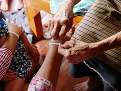 Hand of old woman waving a white string ( Sai Sin ) around her daughter's hand - Thai traditional blessing from an elder one