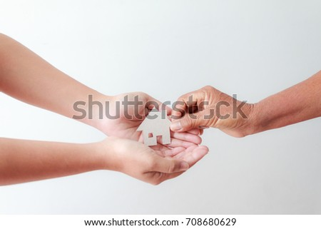 Hand of old women giving paper card house to young woman metaphor and concept for asset heritage of mother and daughter  Stockfoto ©