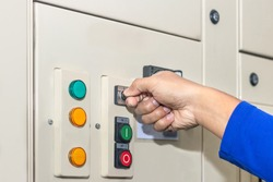 Hand of people key switch select mode in electrical control panel contains switch buttons for operating industrial machine and factory equipment in industry