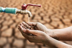 Hand of people wating for a drip of water from a faucet at desert. Climate change, water scarcity and crisis concept.