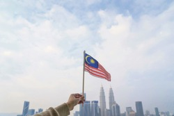 Hand Of Person Holding Malaysia Flag Against Kuala Lumpur view.