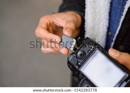 Hand of photographer holding SD memory Card. Male photographer changing SD card of a photo camera outdoors. Young photographer has run out of storage on his memory stick, changes card on his dslr