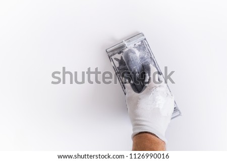 Hand of plasterer at wall polishing. House renovation concept.