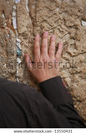 Hand of praying men on the Western Wall filled by wishes in Jerusalem.