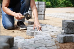 Hand of professional paver worker lays paving stones in layers for pathway, Labor and industry concept.