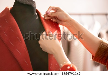 Hand of professional tailor using needle with white thread while sewing collar of red coat for one of clients Foto stock ©