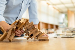 Hand of pulling out wood block fail on building tower. Fail building tower, risk and strategy of project management in business concept.