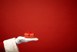Hand of Santa Claus with small red giftbox in isolation