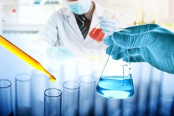 hand of scientist holding flask with dropping yellow liquid to test tube in chemical laboratory background, science laboratory research and development concept