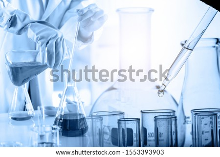hand of scientist holding flask with lab glassware and test tubes in chemical laboratory background, science laboratory research and development concept Stockfoto ©