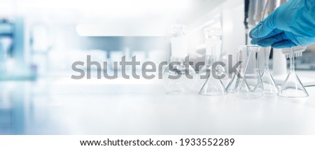 hand of scientist in blue glove with test tube and flask in medical chemistry lab banner background
