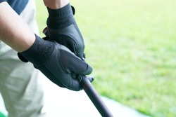 Hand of senior man practicing on golf course