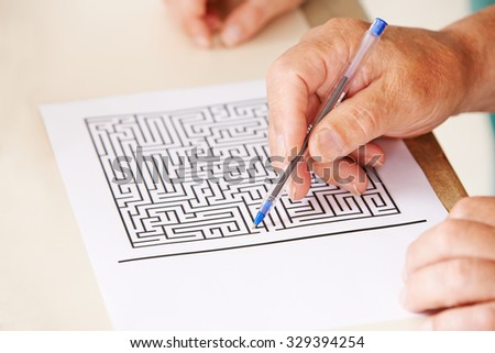 Hand of senior man with pen doing memory training with a paper maze