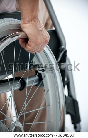 Hand of senior woman on wheelchair