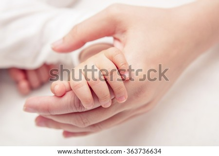 Hand of sleeping baby in the hand of mother close-up on the bed , New family and baby healthy concept