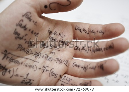 Hand of student with cheat sheet for math exam - selective focus