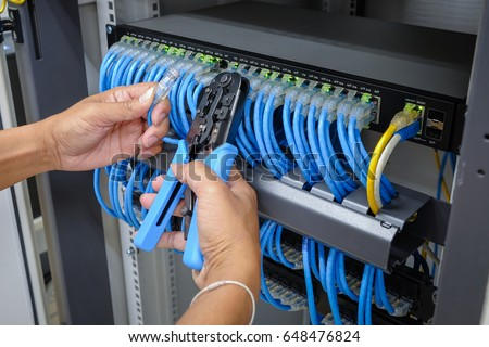 hand of system administrator with network cable connected to patch panel of network gigabit switch and crimping pliers tool Stock photo ©
