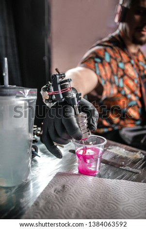 Hand of tattoo artist with a tattoo machine.