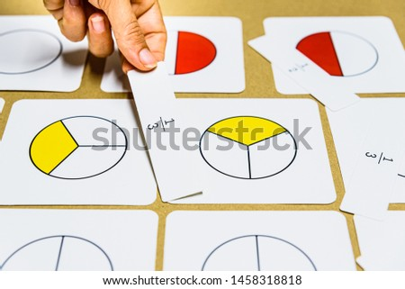 Hand of teacher montessori guide graphically shows fractions with mathematical cards.