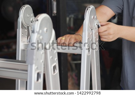 Hand of technician locking Folding Ladder In the open position . convenient ladders ,Light weight, these ladders fold into a compact bundle for storing or carrying.                               stock photo