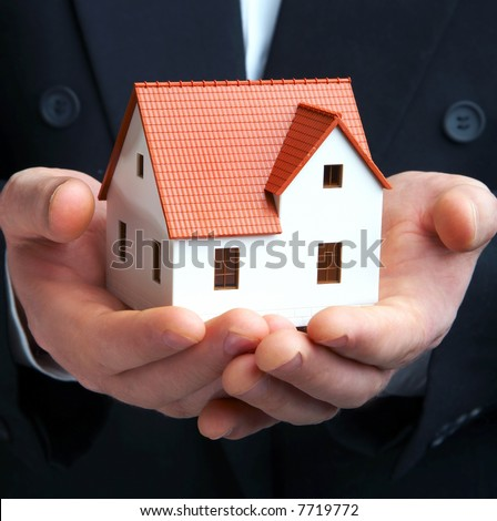 Hand of the businessman with the house - stock photo