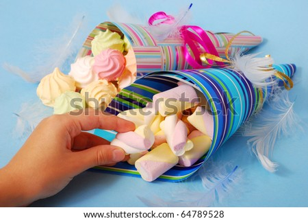 hand of the child reaching for colorful marshmallows and meringues in paper cone