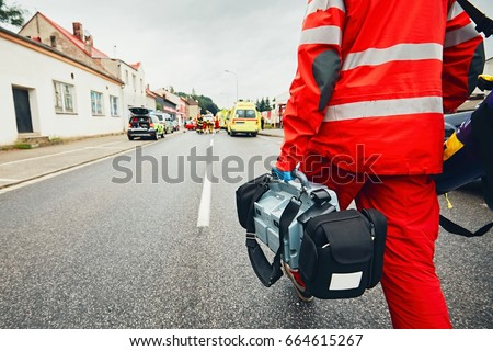 Hand of the doctor with defibrillator. Teams of the Emergency medical service are responding to an traffic accident. #664615267