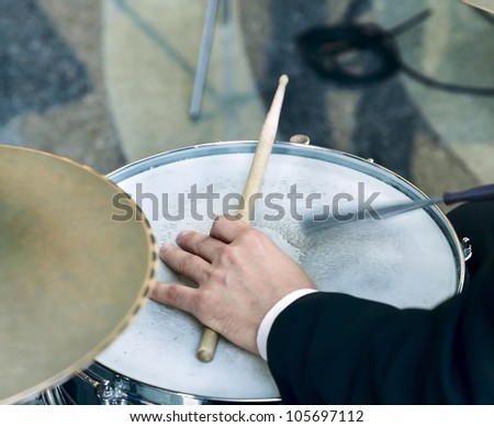 Hand of the drummer playing on drum set