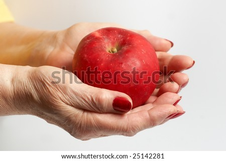 Hand of the elderly lady holding an apple.