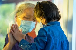 Hand of the grandma and grandchild on a window plane,Protection coronavirus and covid-19 pandemic,Social distancing concept.