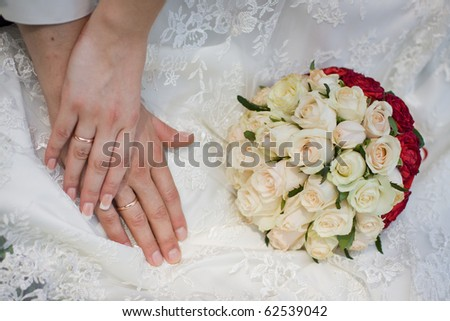 Hand of the groom and the bride with wedding rings near wedding bouquet
