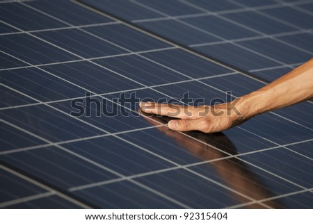Hand of the man touching Solar cell.