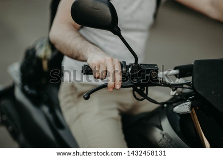 hand of the motorcyclist biker presses the brake on the handle. #1432458131