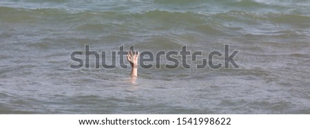 hand of the person during the drowning in the ocean asking for help